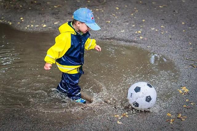 Et barn som leker med ball ute i regnet.