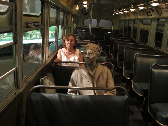 A tired Rosa Parks bravely occupies a 'whites only' seat on the bus that fateful day.