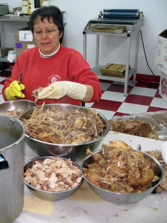 Lady deboning chickens Acadian Rappie Pie