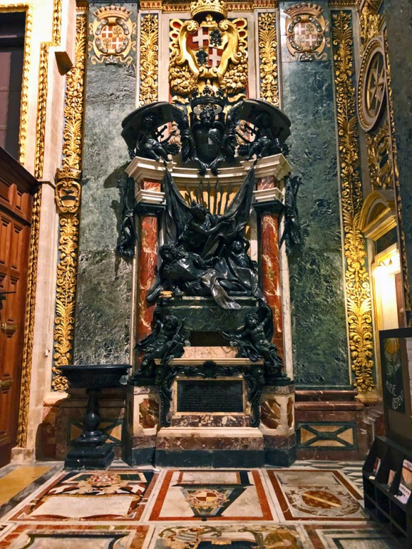 Black marble sculpture marks a tomb with marble tombs lining the floor