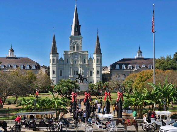 A church in the centre of Jackson Square with horse drawn carriages lined up in front of the gates