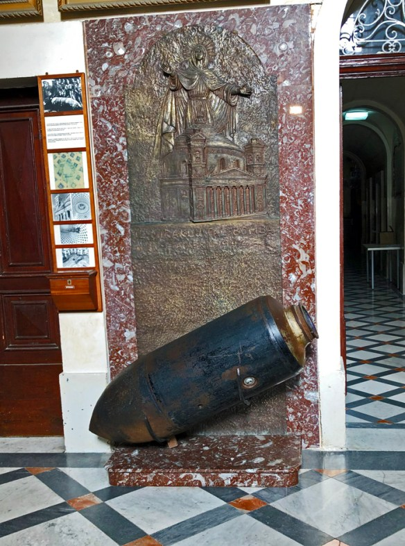 unexploded bomb displayed against a red marble backdrop