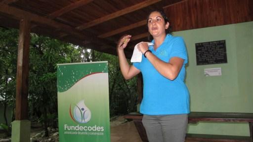 Andrea Prendas wearing blue shirt beside a poster for Funecodes