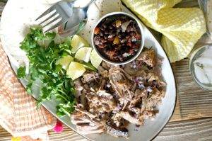 Our Cuban-Style Mojo Slow Cooker Pork Roast bursts with the flavors of citrus, garlic and cilantro.  Fork-tender straight from the crock pot!  Serve over rice or with tortillas for an easy week night meal.