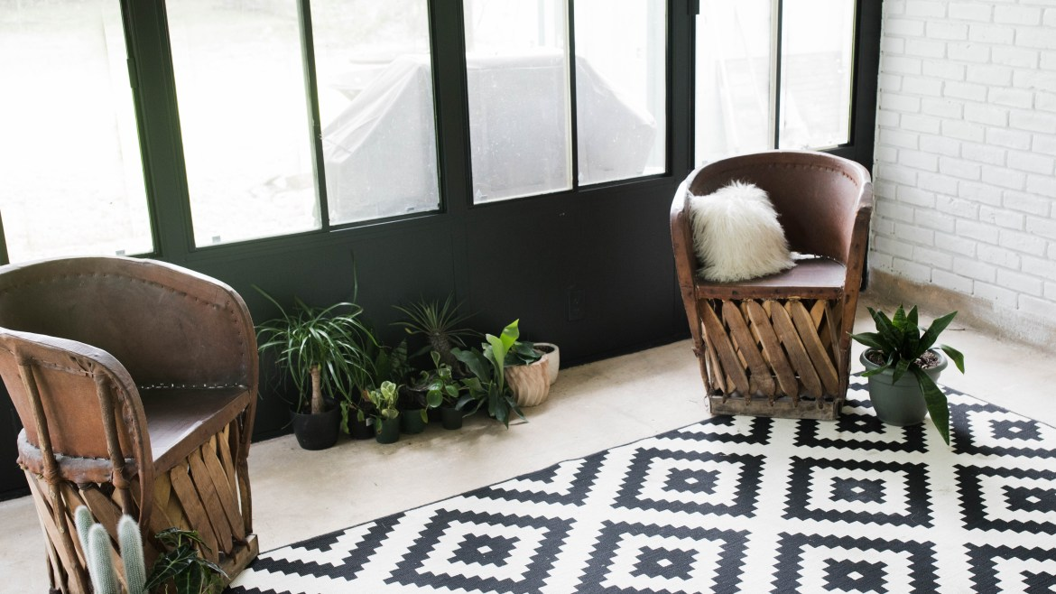 DIY Bohemian Sunroom Makeover // black walls, white painted brick, IKEA geometric rug, Mexican equipale chairs, and plants galore
