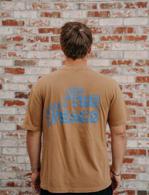 "brown mens tshirt, back says ""peace"""