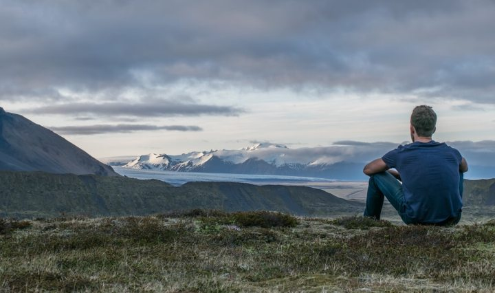 Man sitting on ground looking at mountains and lake