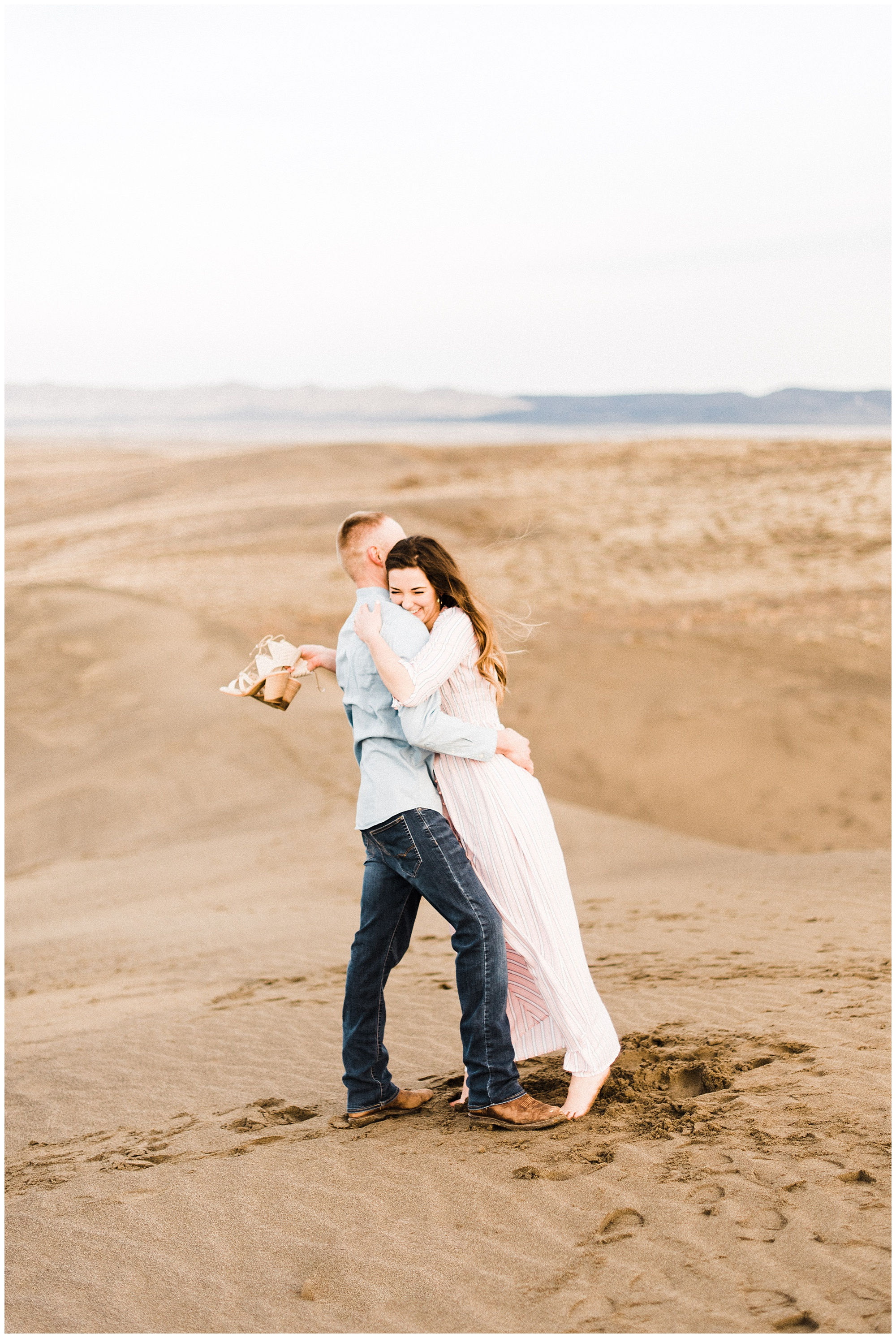 about us section photo of engaged couple on sand dunes by Laura & Devon of Forthright Photo
