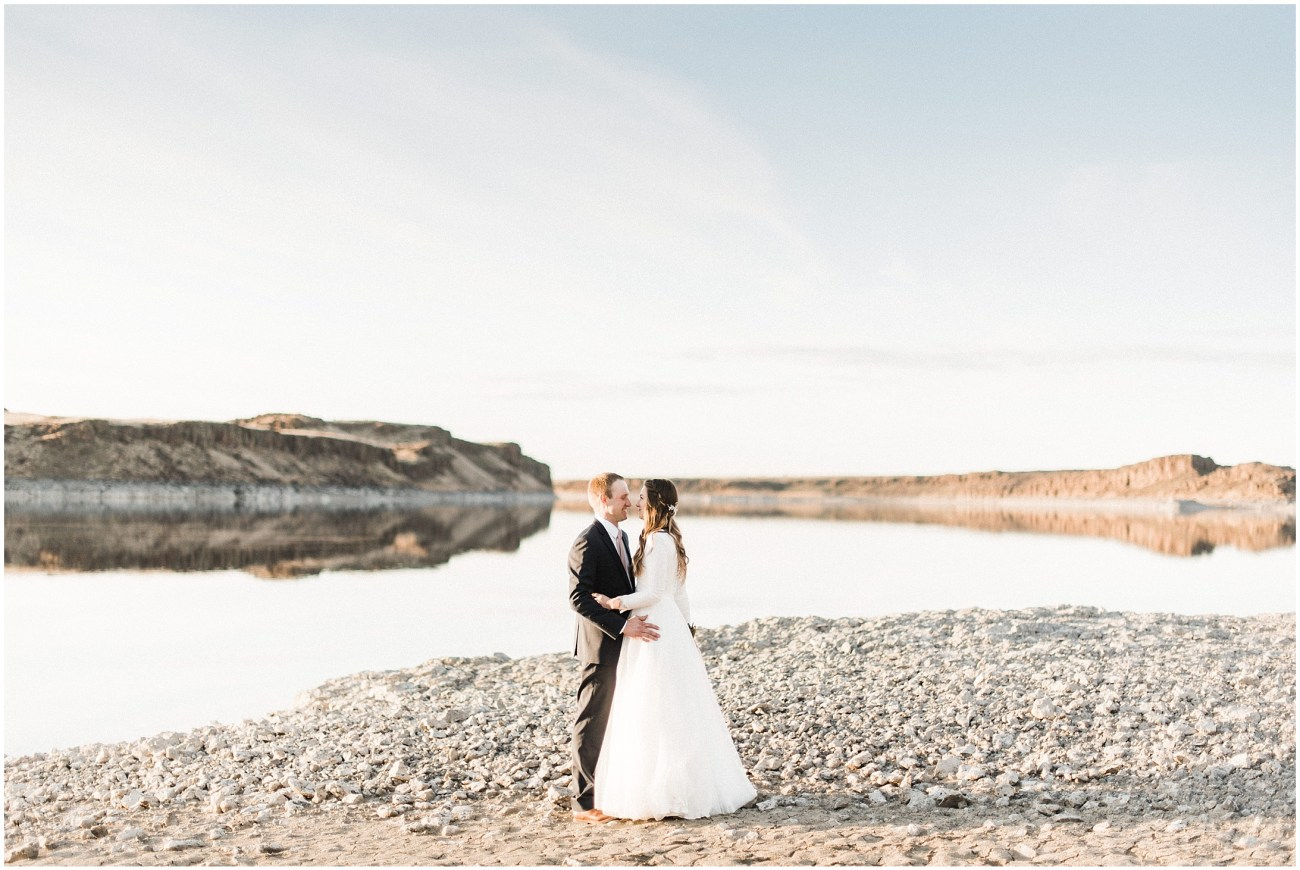 Photo of a bride and groom standing by a desert lake by Forthright Photo