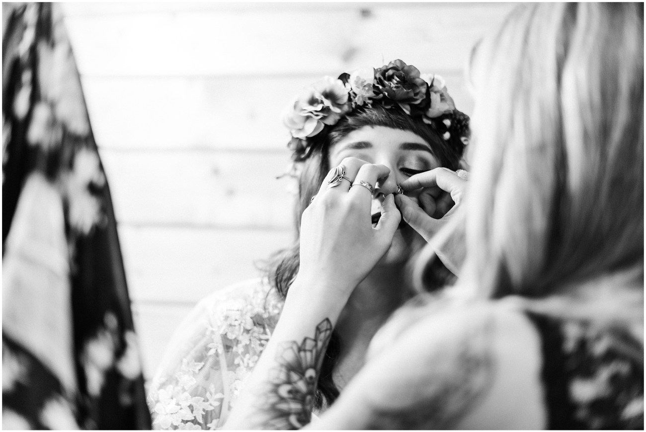 A black & white picture of a bride adjusting her nose rings with the help of a friend
