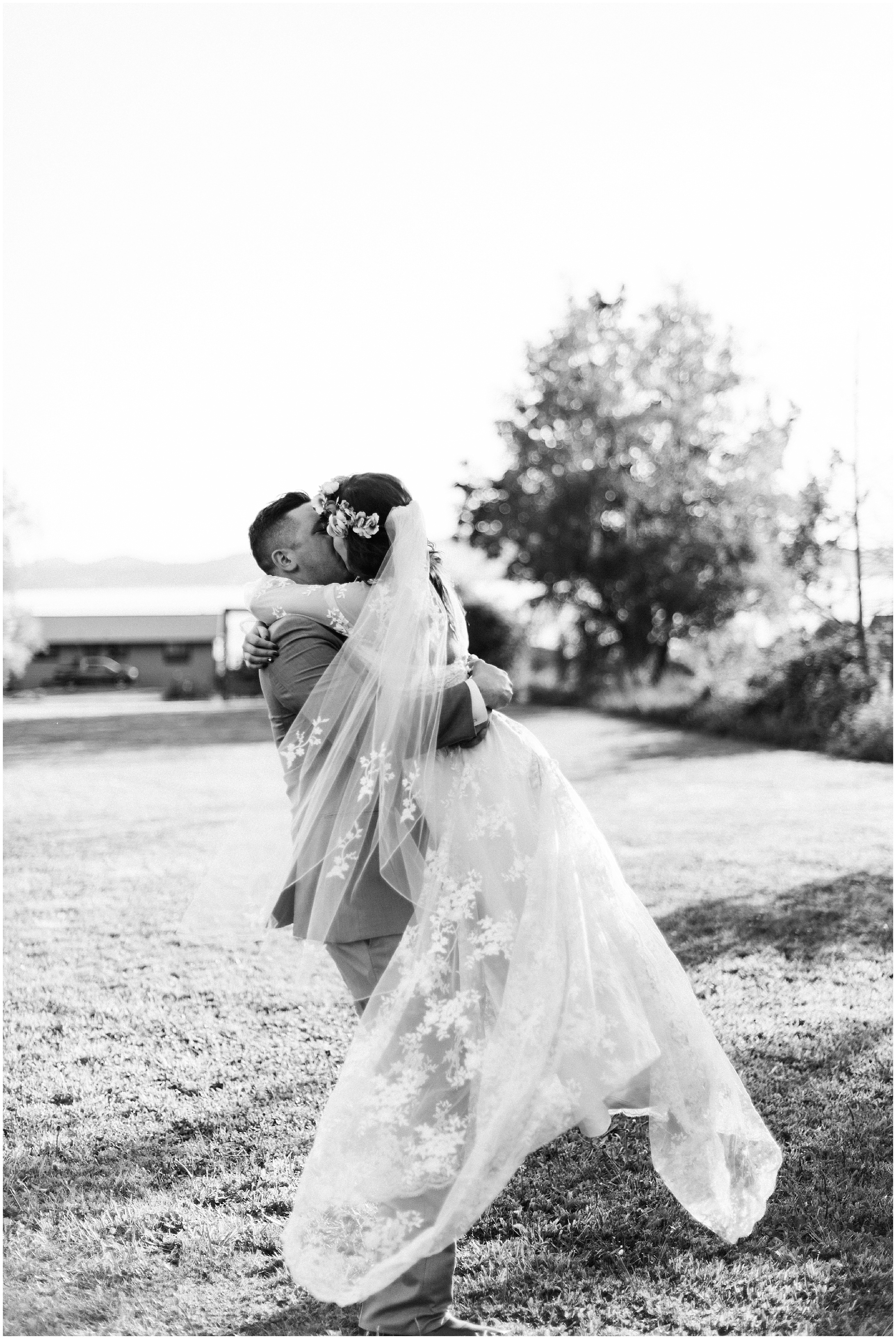 Black and white photo of bride and groom dancing on the lawn of Bayview Civic Hall during their wedding reception in Bayview, WA
