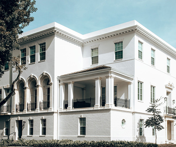 A white-painted brick mansion with bullet resistant windows throughout