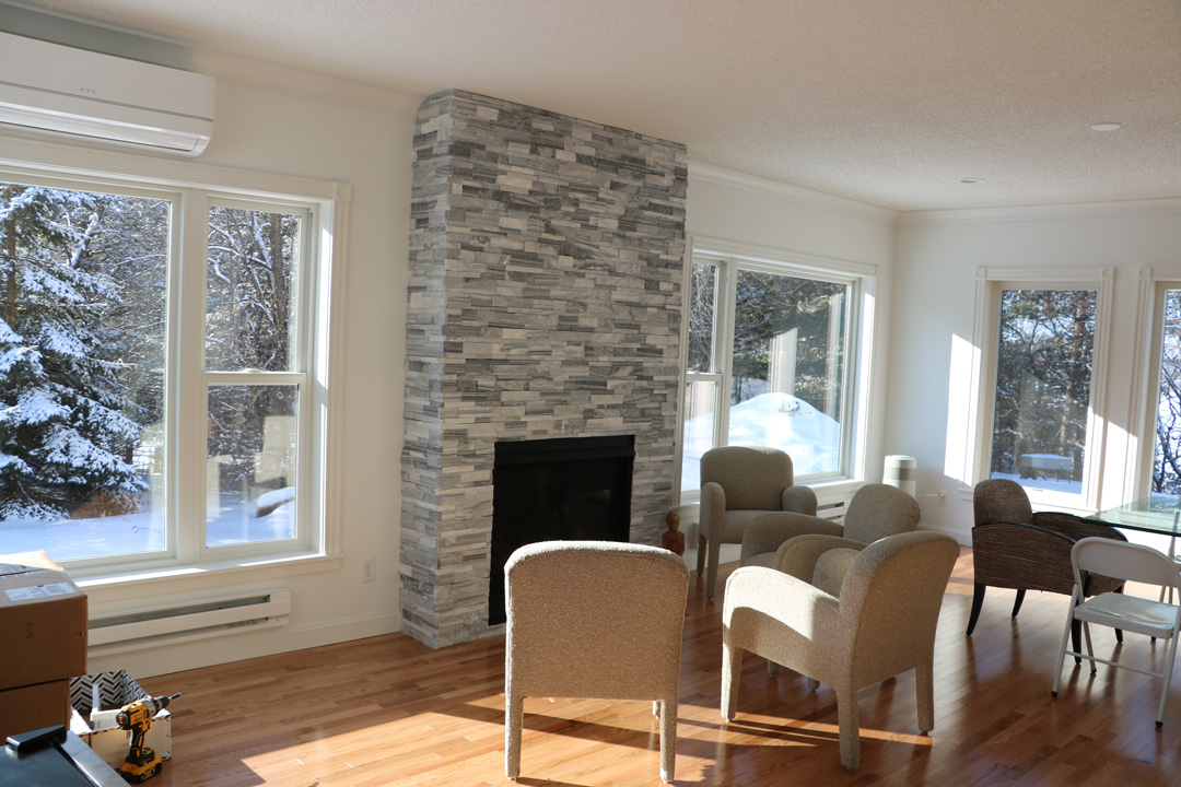 Gray stone fireplace with chairs around it.
