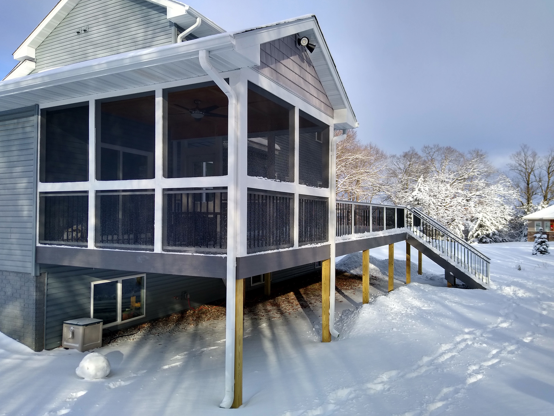Screen porch addition with snow on grass