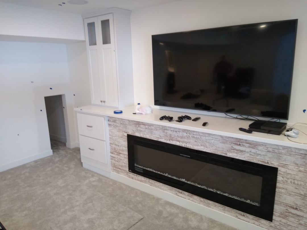 tv with fireplace underneath and cabinets