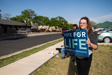 Kiran Thompson holds a sign supporting Proposition A across from the Lubbock Planned Parenthood location on April 27, 2021, in Lubbock.