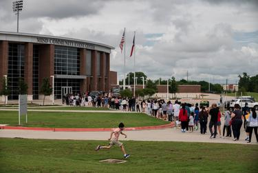 A young boy jumps over a drainage fence as McKinney ISD students and their legal guardians stand in a line to receive a COVID-19 vaccine at the McKinney ISD Stadium and Community Event Center on May 20, 2021.