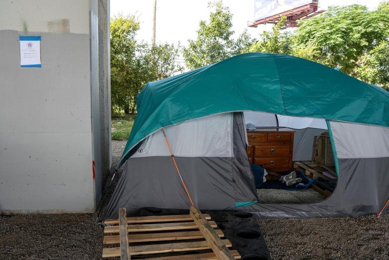 """A """"Notice of Cleanup and Property Removal"""" sign hangs on a pillar next to a tent underneath Ben White Blvd. on July 27, 2021."""