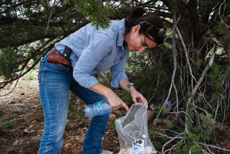Hudspeth County Administrator Joanna Mackenzie picks up water bottles and a burrito left behind along a trail frequented through the harsh terrain by people that are attempting to avoid detection by the United States Border Patrol in Hudspeth County on August 11, 2021.
