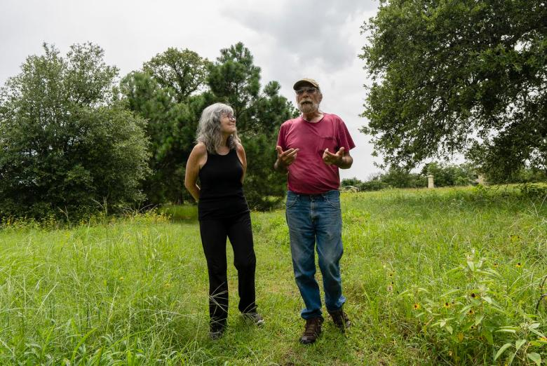 From left, Leslie Scouras, 63, and her husband Bob Scouras, 72, walk a path on their property in Lee County on July 12, 2021. The Scourases are two of many Lee County residents whose water sources have dried up as a result of Vista Ridge Pipeline Project.