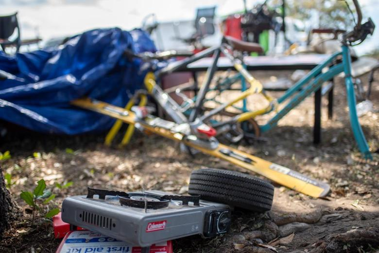 A propane burner sits near bike parts near a former homeless encampment on Riverside Drive on Sept. 28, 2021 in Austin. Many of the people who had been living in the camp said they weren't given enough notice and were not offered any place to stay.