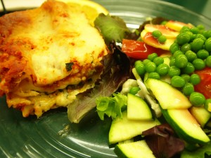 A photo of lasagna and salad from Sunshine Health Foods