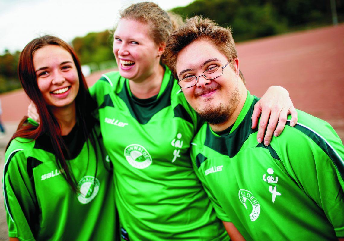 Drei Jugendliche auf dem Sportplatz
