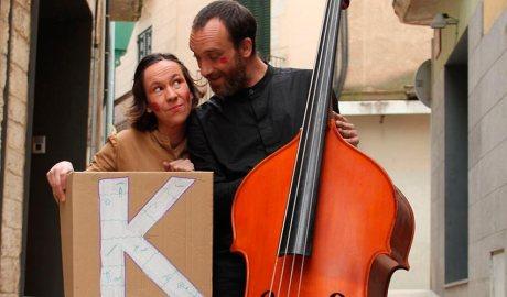 Imatge de l'espectacle Kaixes. Una noia aguanta una caixa amb una K pintada en blanc i un noi aguanta un contrabaix