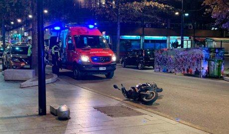 Un ciclomotor al terra davant d'una ambulància dels Bombers