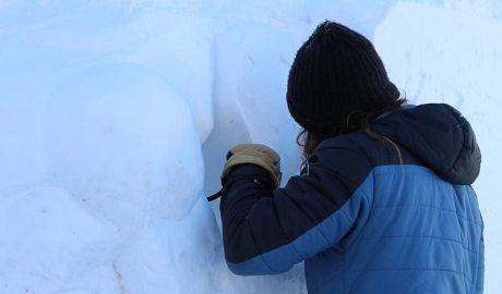 Un escultor treballa amb un bloc de neu