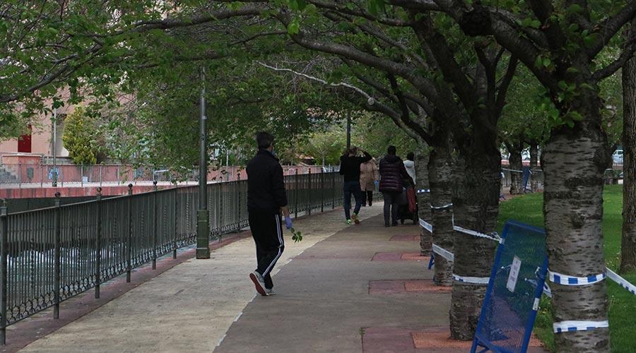 Gent passejant pel costat del Parc Central el primer dia d'excepció al confinament