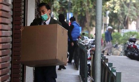 Home amb mascareta i una caixa