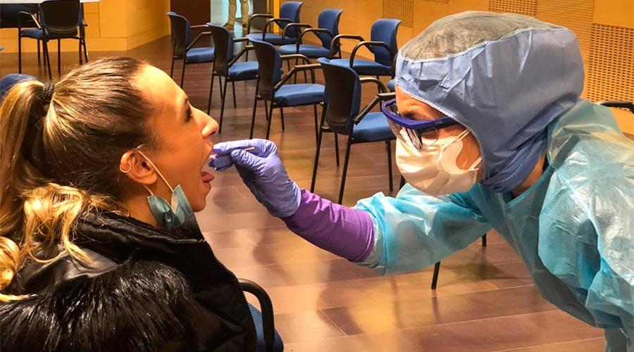 Un sanitari obté mostres d'una dona per fer una prova TMA o PCR
