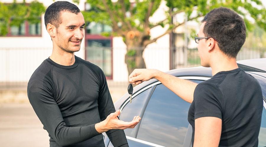 Dos joves en una compravenda d'un cotxe