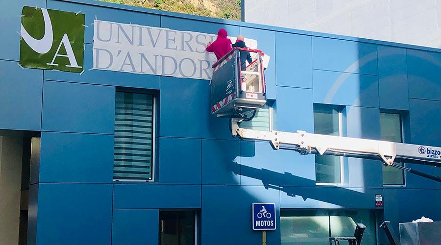 Uns operaris comencen a instal·lar la retolació exterior de l'edifici Cub de la Universitat d'Andorra. Foto: UdA.