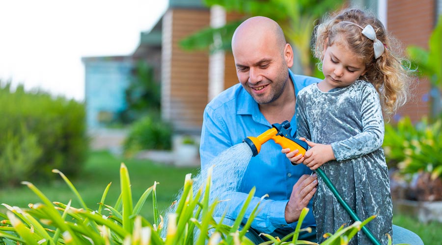 Pare i nena regant el jardí
