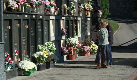 Dues persones visiten els seus familiars als cementiri el dia de Tots Sants del 2020