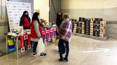 Unes persones recollint un lot d'aliments i productes al local de la Creu Roja