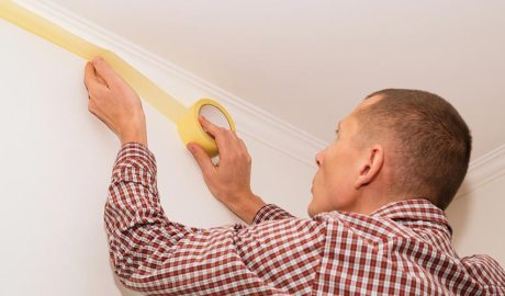 Un home posant cinta en una paret per a pintar-la