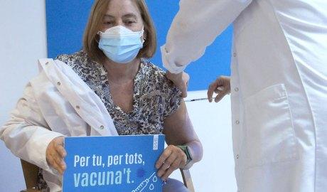 Una professional sanitària rebent la vacuna de Covid-19 i aguantant un cartell animant a la vacunació
