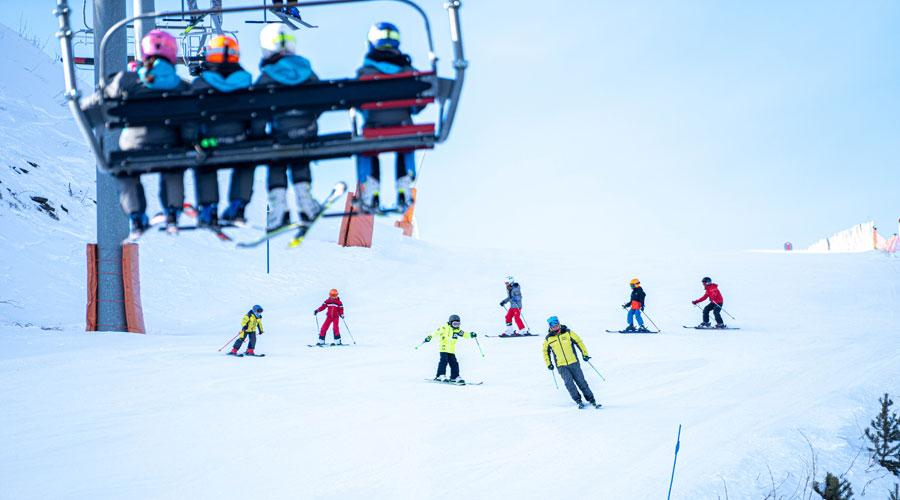 Telecadira i infants esquiant