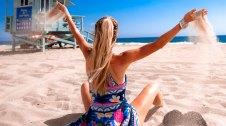 Noia amb cabellera rossa i cua a la platja