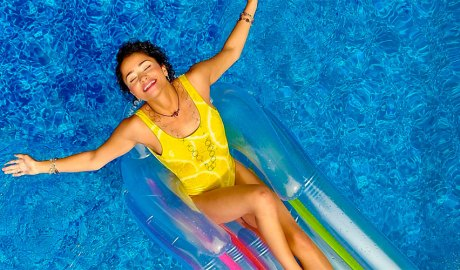 Noia en una barca inflable en una piscina