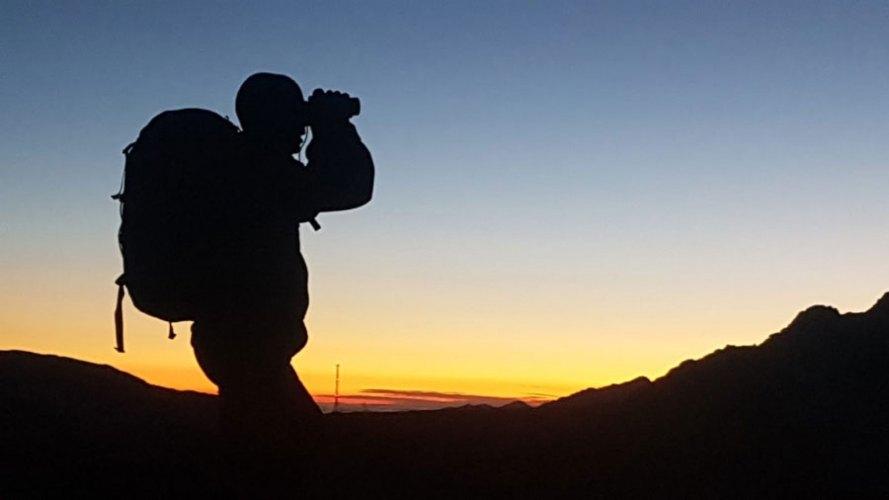 Una persona carregada amb motxilla observant a través de prismàtics