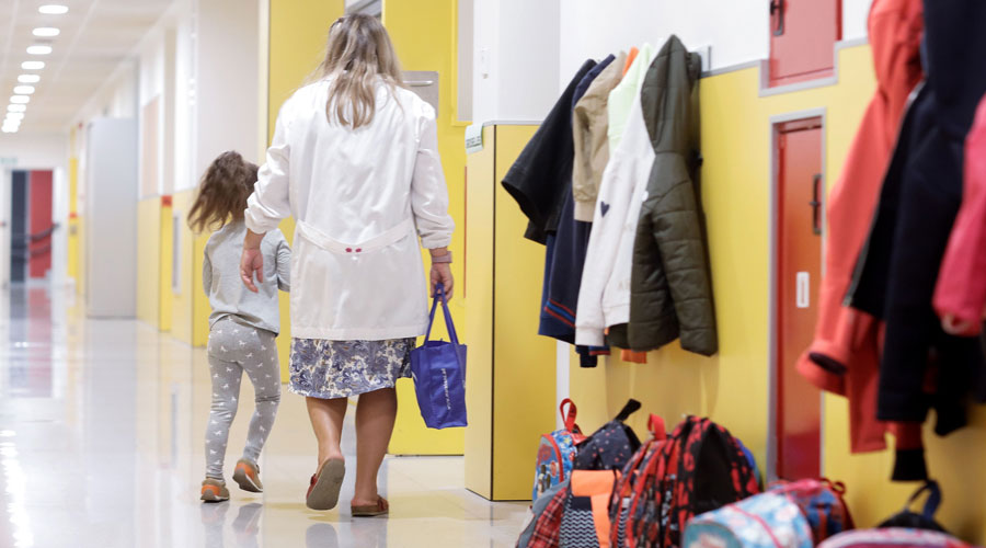 Una professora acompanya una alumna a l'aula