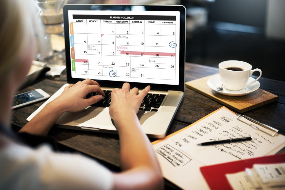 Mujer sentada frente a monitor con calendario digital