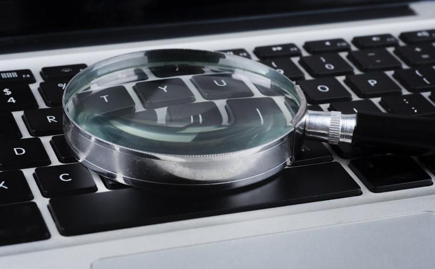 una lupa sobre un teclado de laptop - búsqueda de información