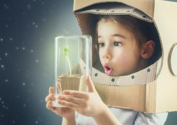niña con una casco de austronauta de cartón sostiene una planta - imaginación