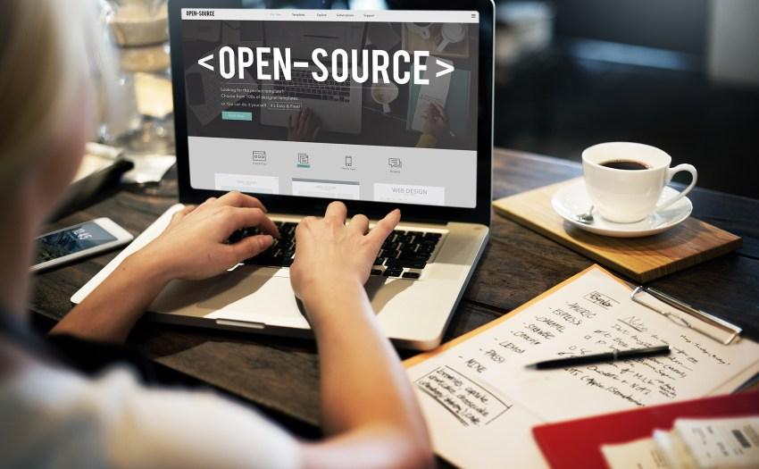 Persona escribiendo en un teclado de laptop con la palabra open source en la pantalla
