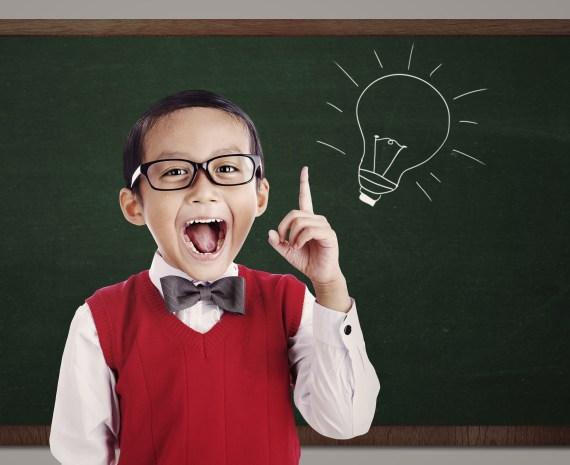 Un niño feliz parado frente a una pizarra con una bombilla dibujada - invención